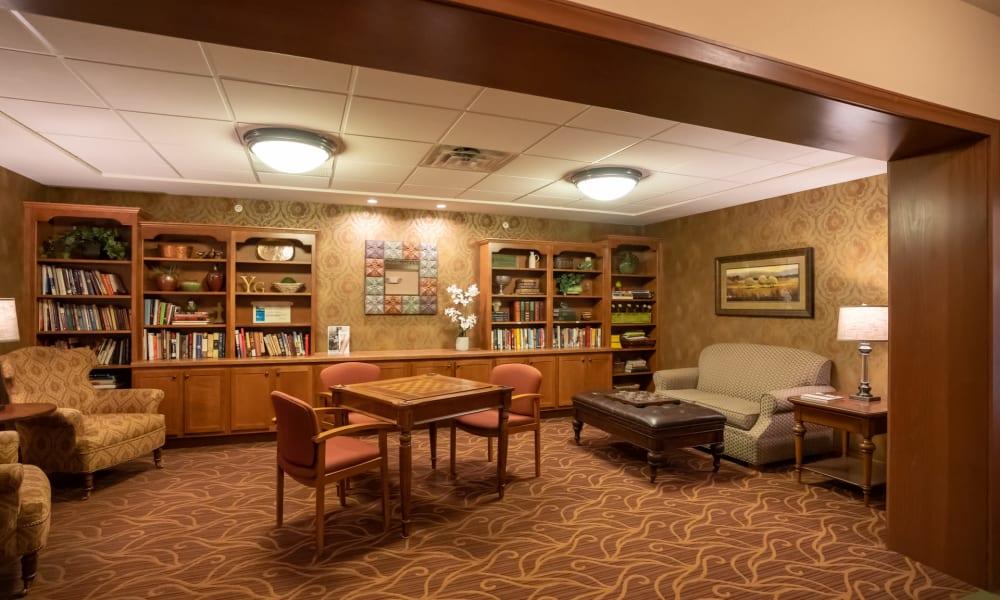Warmly lit lounge area with several full bookshelves at York Gardens in Edina, Minnesota