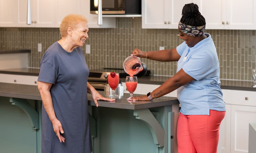 A caregiver helps a resident with a smoothie in a therapy kitchen at Seasons Memory Care at Rolling Hills in Torrance, California