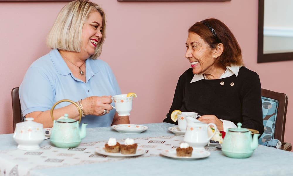 A resident and a caregiver enjoying afternoon tea at Seasons Memory Care at Rolling Hills in Torrance, California.