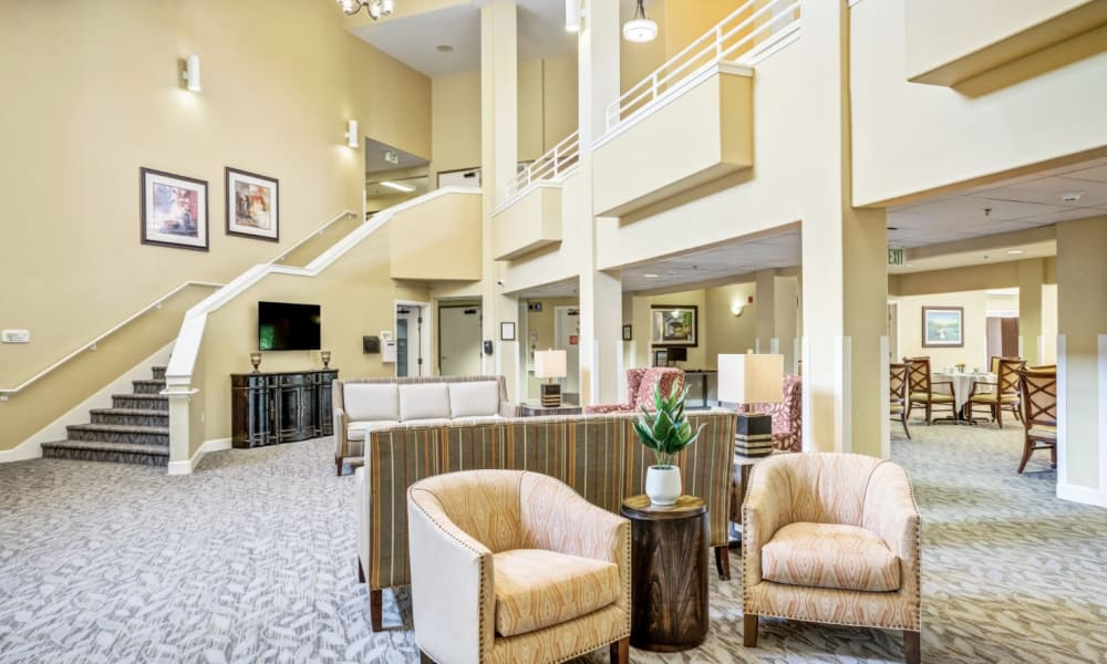 Lobby with an elegant staircase at Woodside Senior Living in Springfield, Oregon