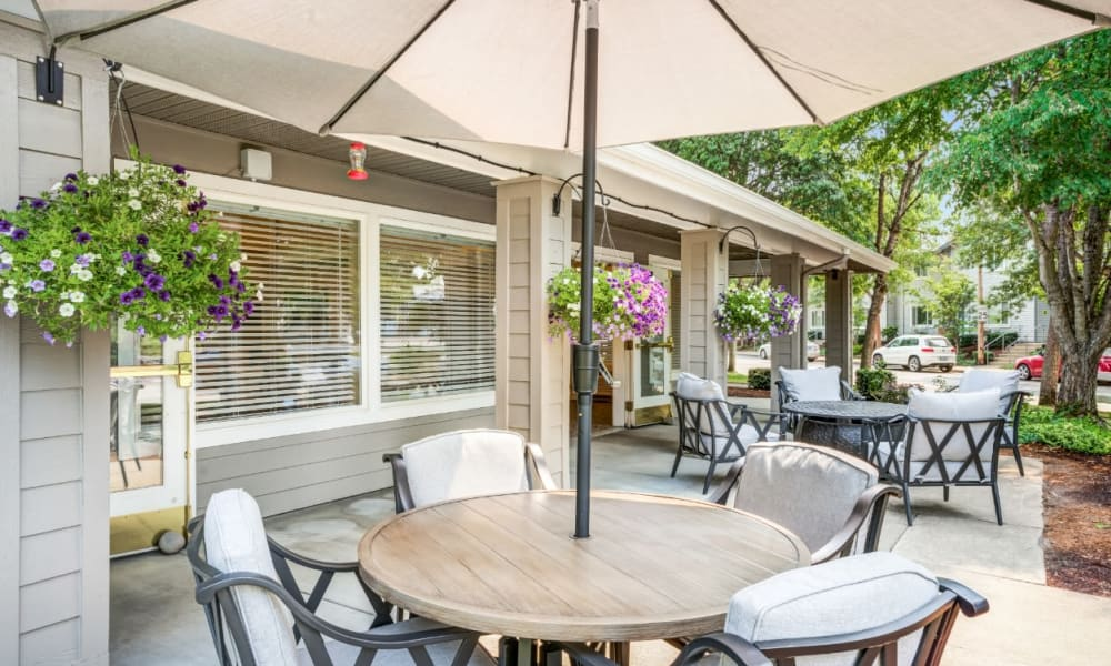 Table with an umbrella on the patio at Woodside Senior Living in Springfield, Oregon