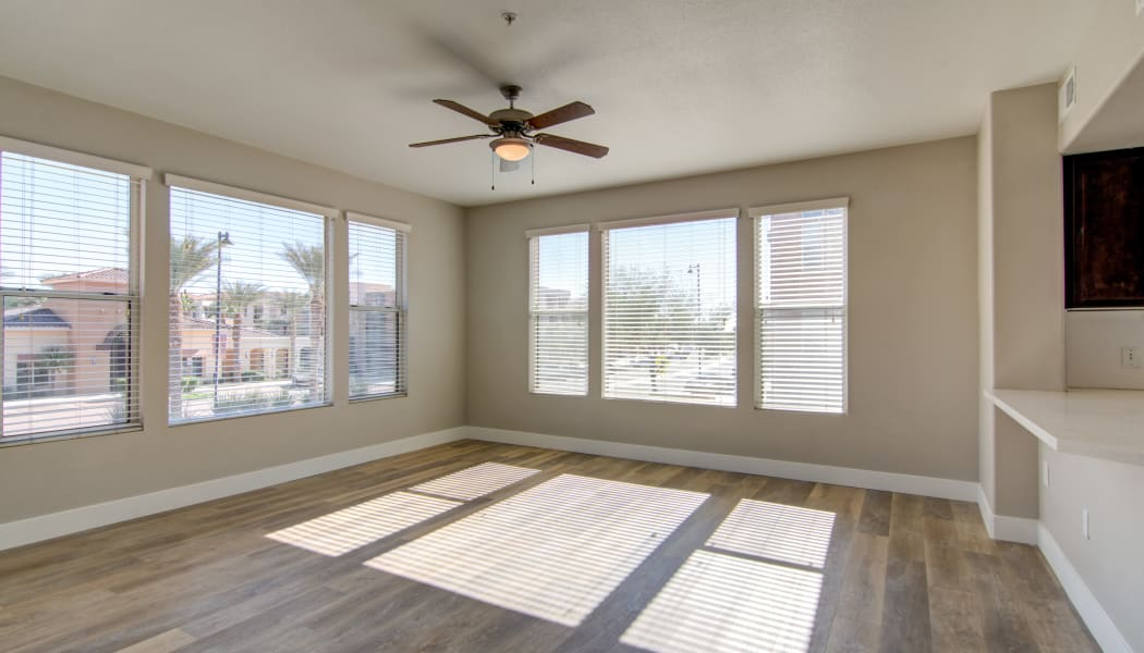 Hardwood floors and a ceiling fan in the open-concept living area of an apartment home at The Residences at Stadium Village in Surprise, Arizona