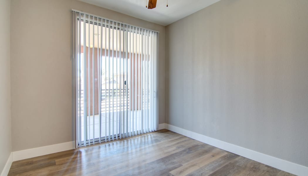 Ceiling fan, hardwood floors, and a sliding door to the private patio outside an apartment home's bedroom at The Residences at Stadium Village in Surprise, Arizona