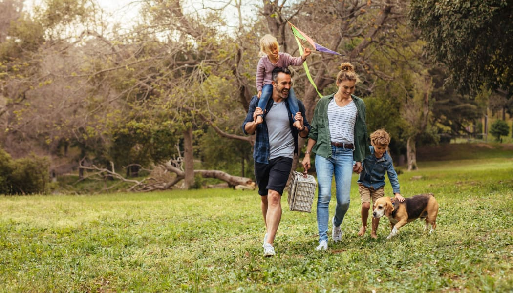 Family walking their dog in a local park in Lubbock, Texas near Tuscany Place