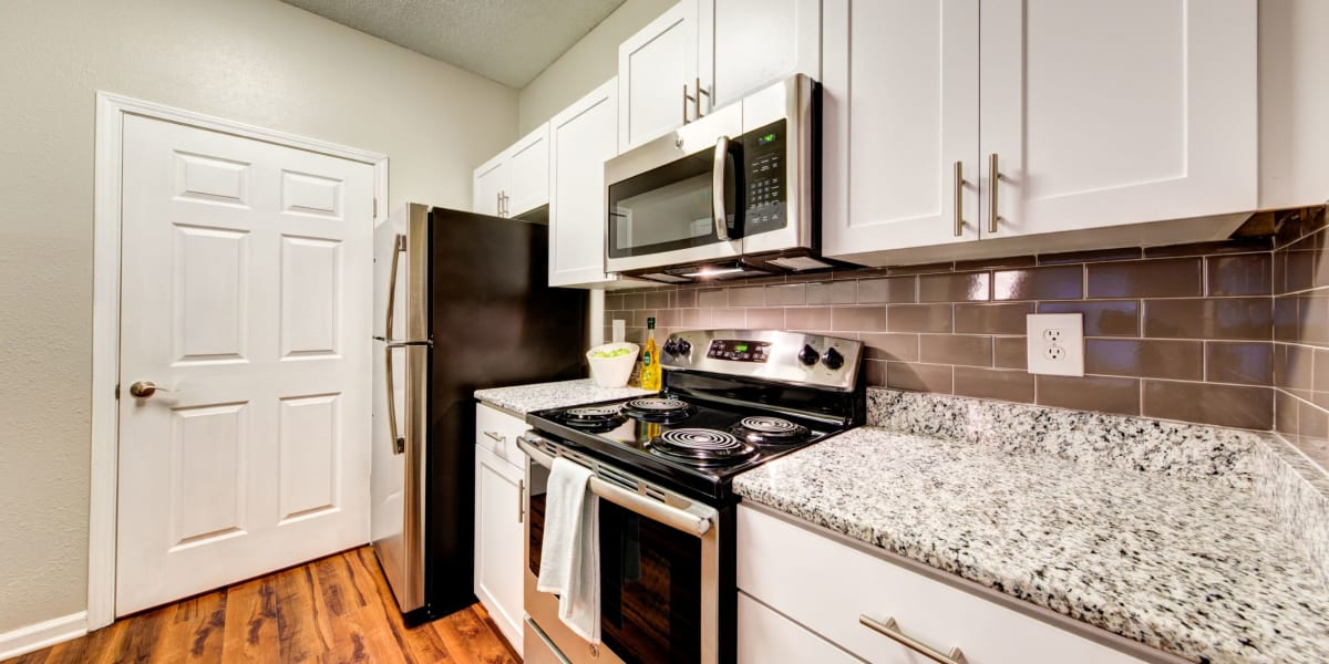 Open kitchen with granite counters, stainless steel appliances, and wood flooring at Marquis on Edwards Mill in Raleigh, North Carolina