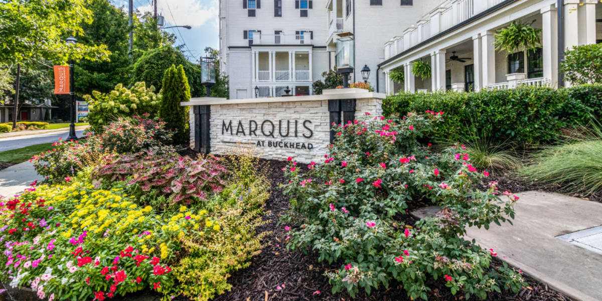 Property sign surrounded by a variety of flowers and plants at Marquis at Buckhead in Atlanta, Georgia
