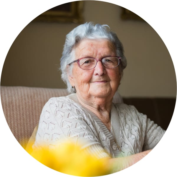 Skilled Nursing resident sitting in a chair and smiling at a Oxford Senior Living location