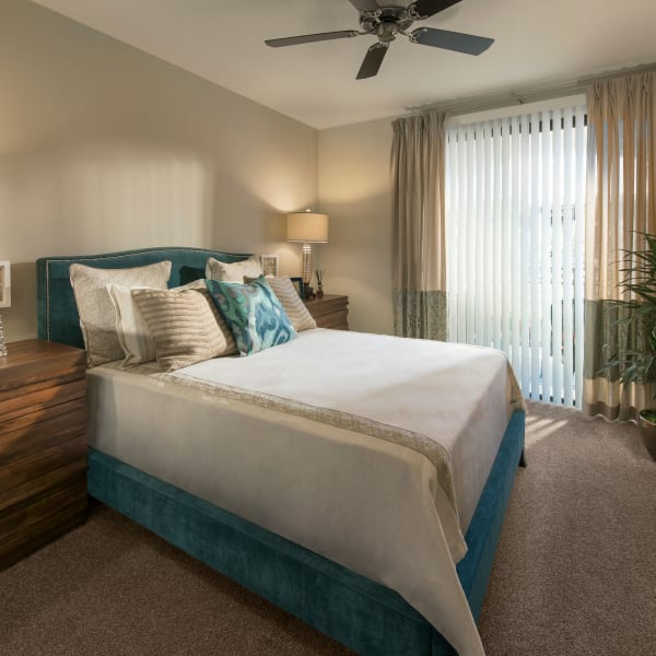 Well-decorated master bedroom with ceiling fan and sliding door to private balcony of model home at San Travesia in Scottsdale, Arizona