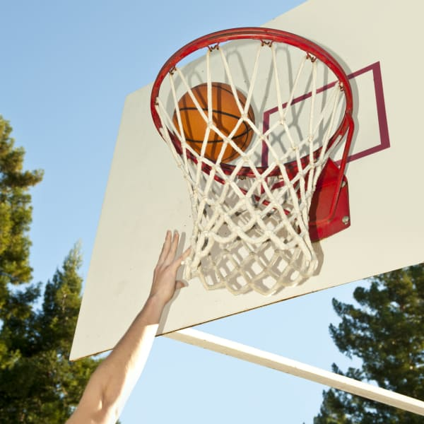 Resident playing basketball on a beautiful day at Pine Tree Apartments in Chico, California