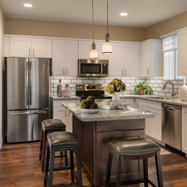 Modern kitchen with stainless-steel appliances in model home at San Piedra in Mesa, Arizona