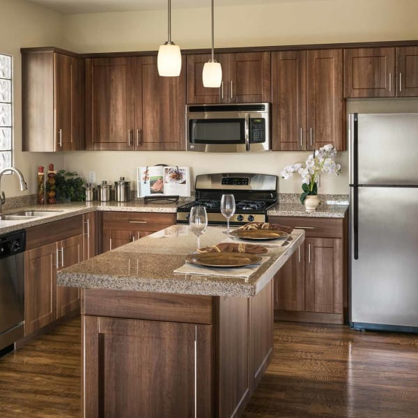 Contemporary kitchen with island with beautiful hardwood flooring at San Hacienda in Chandler, Arizona