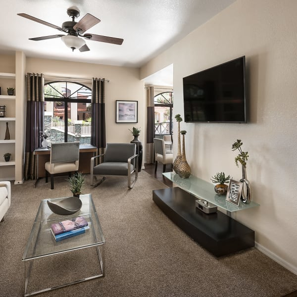 Living room with a ceiling fan in model home at San Lagos in Glendale, Arizona