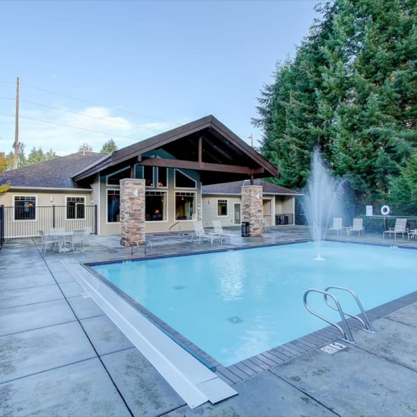Spacious pool with a sundeck and chairs at The Dakota Apartments in Lacey, Washington