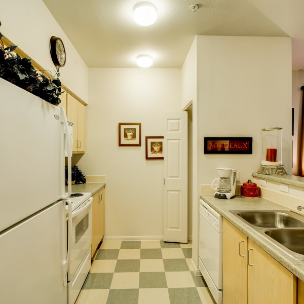 Kitchen with white appliances and a stainless-steel sink at The Dakota Apartments in Lacey, Washington