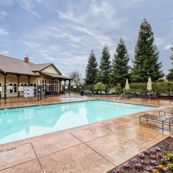 Large swimming pool with a sundeck, tables, and chairs at Laguna Creek Apartments in Elk Grove, California