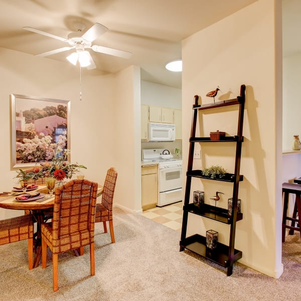 Dining room with plush carpeting and ceiling fans at Laguna Creek Apartments in Elk Grove, California