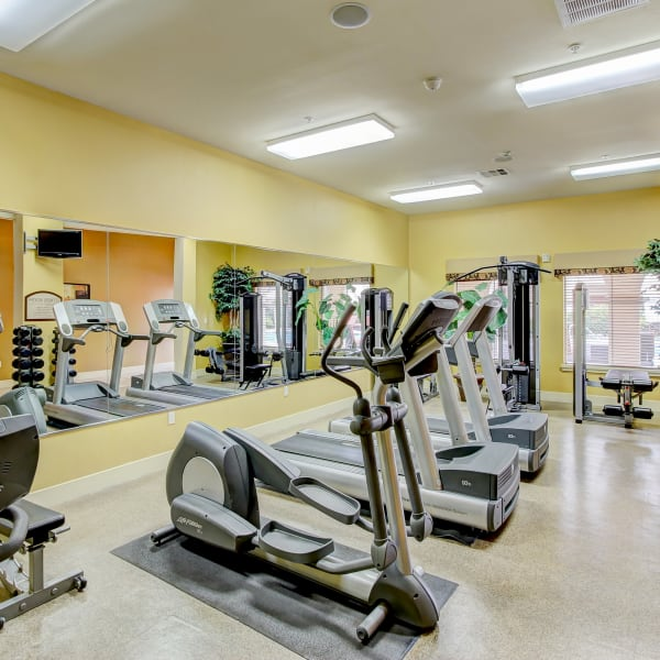 Fitness center with individual workout stations and a body-sized mirror at Monticello at Southport in West Sacramento, California