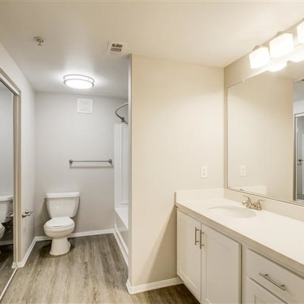 Spacious bathroom with a large vanity mirror and oval bathtub at Monticello at Southport in West Sacramento, California