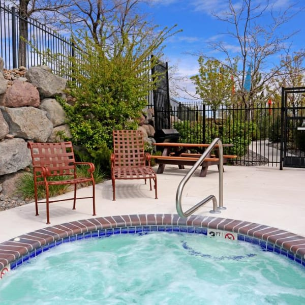 Outdoor hot tub with a table and chairs at Northwind Apartments in Reno, Nevada