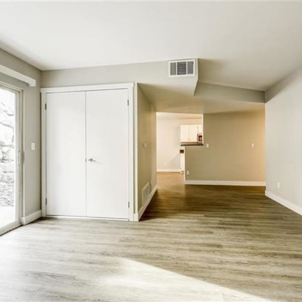Spacious living room with wood-style flooring and back patio access at Northwind Apartments in Reno, Nevada