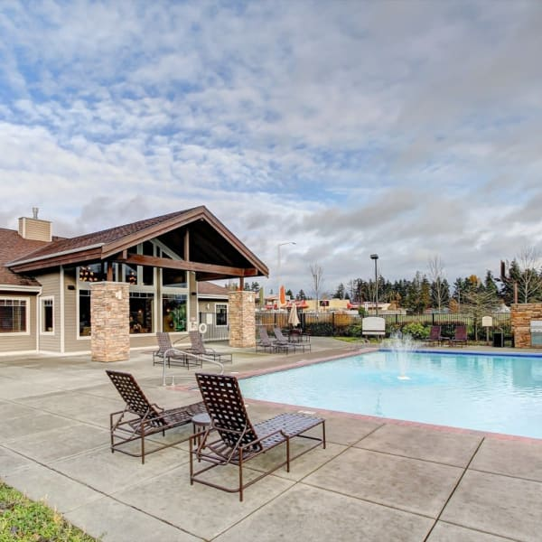 Pool with a large pool deck and lounge chairs at The Meadows in Tacoma, Washington