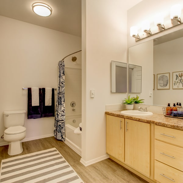 Spacious bathroom with a large vanity mirror at The Meadows in Tacoma, Washington