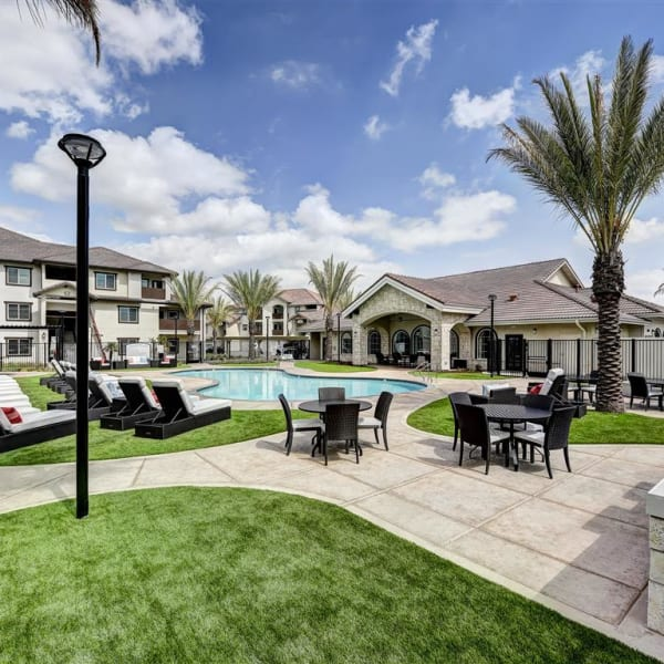 Resort style swimming pool surround by a grass lawn for sunbathing at The Palms at Morada in Stockton, California