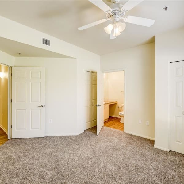 Master bedroom with plush carpeting and ceiling fan at Tierra Pointe in Casa Grande, Arizona