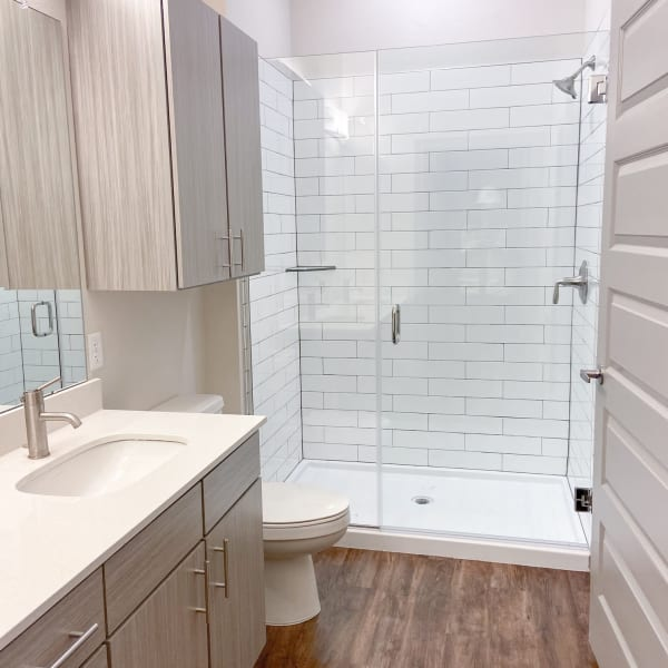 Bathroom with walk in shower featuring white tile, glass door and dark wood patterned floor at The Alcott in Denver, Colorado
