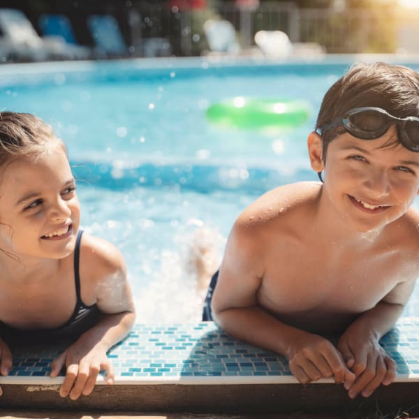 Brother and sister having a ball at the pool at El Potrero Apartments in Bakersfield, California