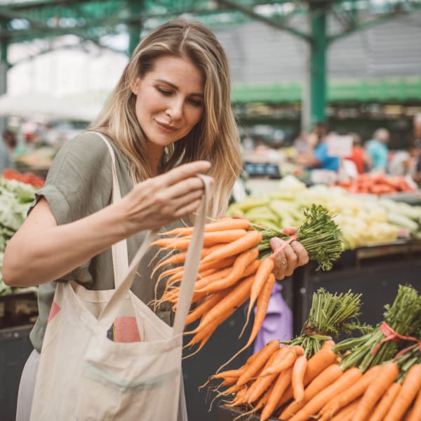 Resident picking up fresh produce at a farmers market near Olympus Auburn Lakes in Spring, Texas
