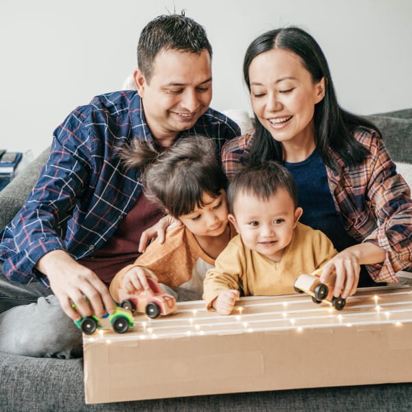 Parents showing their toddler children how to play with some toys in their apartment at Olympus Auburn Lakes in Spring, Texas
