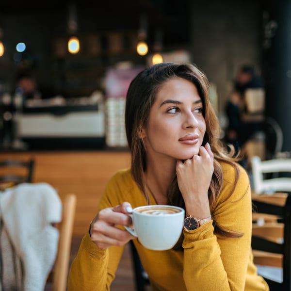 Resident savoring her latte at her favorite café near Olympus Carrington in Pooler, Georgia