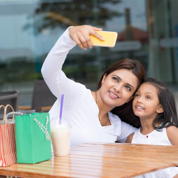 Mother and daughter taking a selfie while taking a break from shopping downtown near Olympus Katy Ranch in Katy, Texas