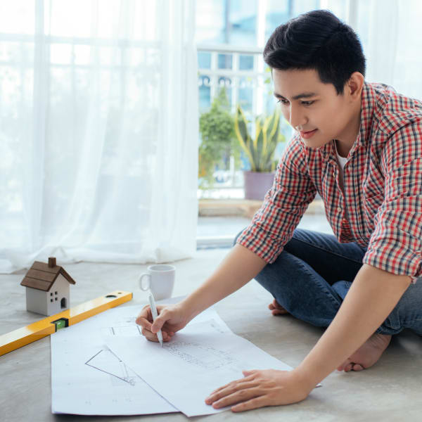 Resident architect drawing up some plans on the floor of his new luxury apartment at Olympus Las Colinas in Irving, Texas