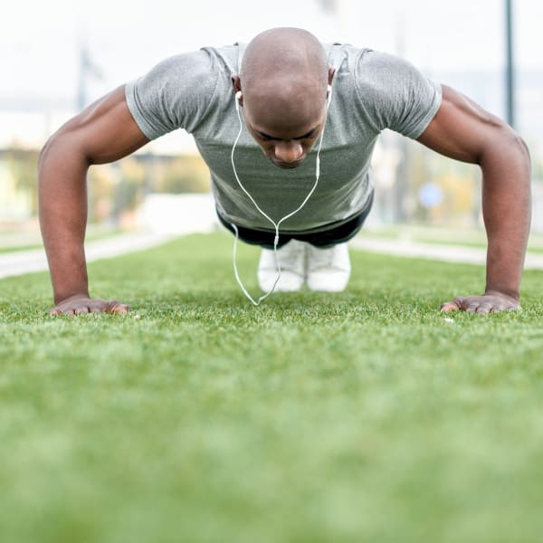 Resident doing some pushups at a sports field near Olympus Town Center in Keller, Texas