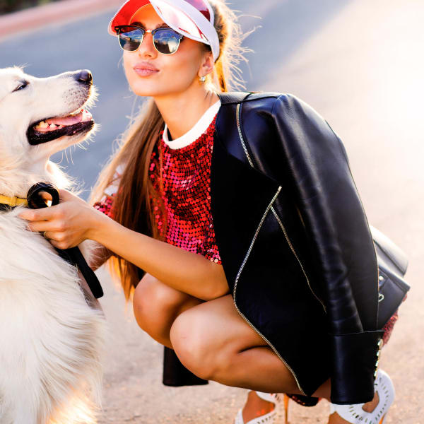 Resident and her dog posing for a picture outside at Tacara at Westover Hills in San Antonio, Texas