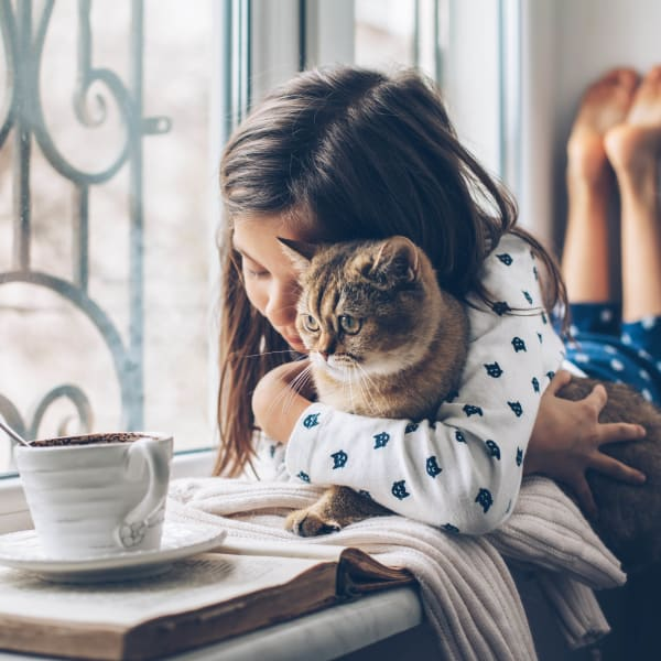 Child and her kitten reading by the window in their home at The Enclave in Brunswick, Georgia