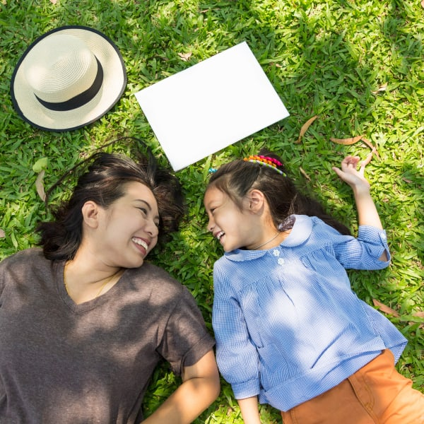 Mother and daughter relaxing on the green grass outside at Olympus Woodbridge in Sachse, Texas