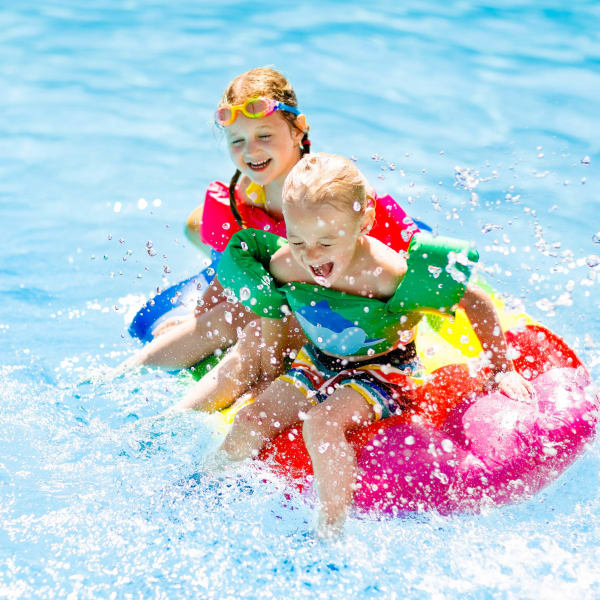 Children having a ball in the swimming pool at Olympus Woodbridge in Sachse, Texas
