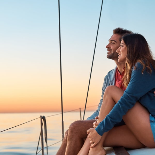 Couple enjoying the sunset from their sailboat near at Portside Ventura Harbor in Ventura, California