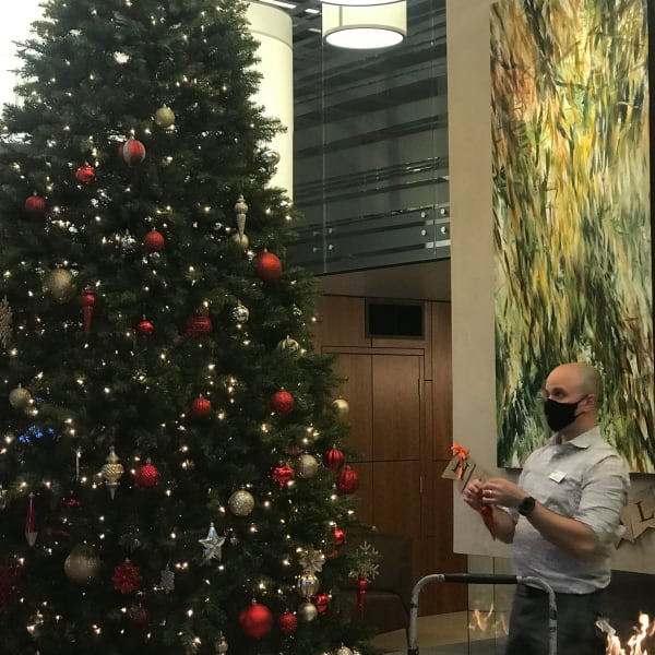 Employee setting up a Christmas tree at The Century in Seattle, Washington