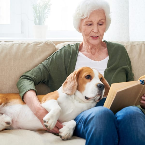 A resident reading to her dog at Pacifica Senior Living Sterling in Sterling, Virginia.