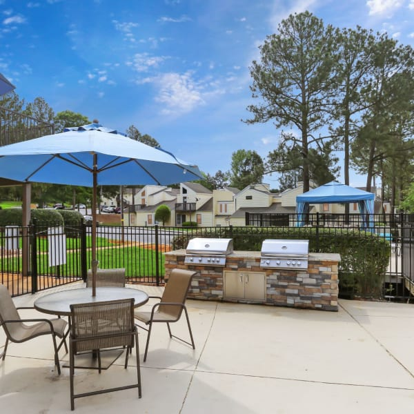 BBQ area next to the pool with seating and umbrellas at the tables at The Flats at Arrowood in Charlotte, North Carolina