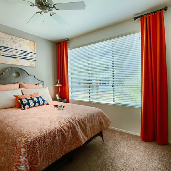 Well-decorated master bedroom with ceiling fan and bathroom at Cactus Forty-2 in Phoenix, Arizona