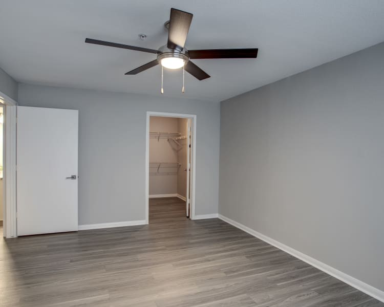 Hardwood floors, walk-in closet, and ceiling fan in bedroom of recently renovated home at Kenwood Club at the Park in Katy, Texas
