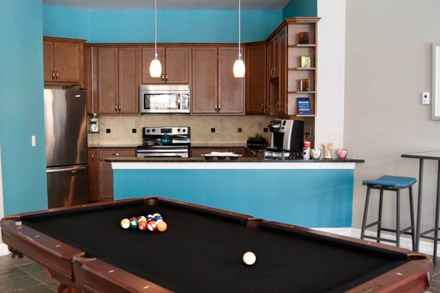 Closeup view of billiards table and clubhouse kitchen in the background at The Club at Stablechase
