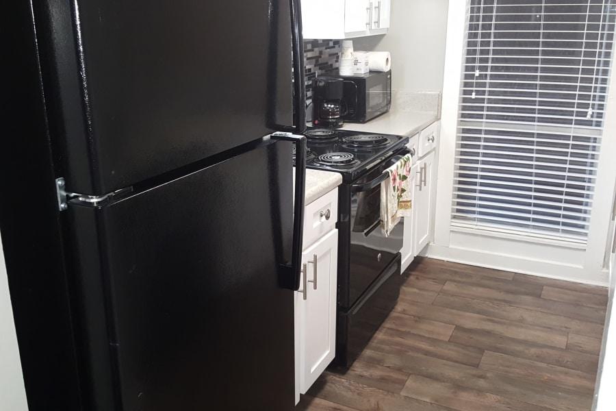 Modern kitchen with black appliances at Pier 5350 in Jacksonville, Florida