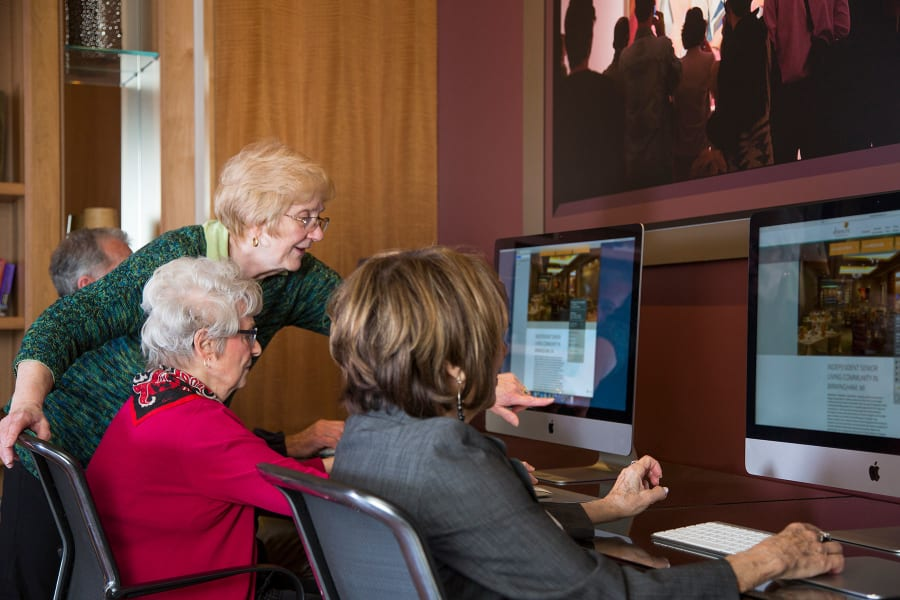 Residents using the Apple computers in the business center at Casa Del Rio Senior Living in Peoria, Arizona