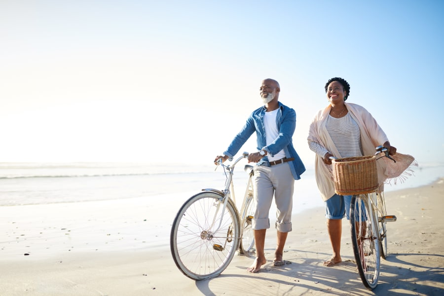 Resident couple walking their bikes on the beach near Carmel Village in Fountain Valley, California